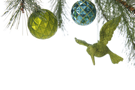 boughs: A top boarder under the boughs of a decorated Christmas tree, revealing a round green and blue bulb and a sparkly green humming bird ornament.  On a white background. Stock Photo