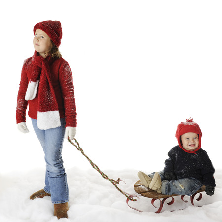 An elementary girl pulling her baby brother on a sled.  On a white backghround with plenty of space for your text over sled.   Stock Photo - 22450257