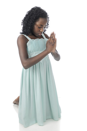 bowed head: A beautiful preteen kneeling in prayer, her eyes closed, head bowed and hands clasped.  On a white background.