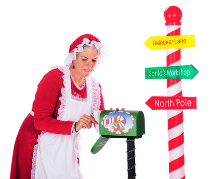 Mrs. Claus getting mail from Santas mailbox next to a candy striped pole with directions to Santa.  On a white background. Imagens