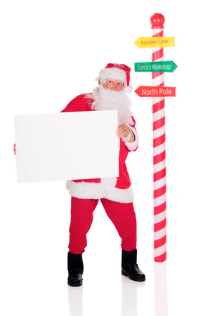 Santa Claus standing by a candy striped pole while holding a blank sign.  On a white background. photo