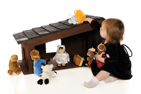 An adorable baby girl playing with a large soft scuptured Nativity Set.  Isolated on white.