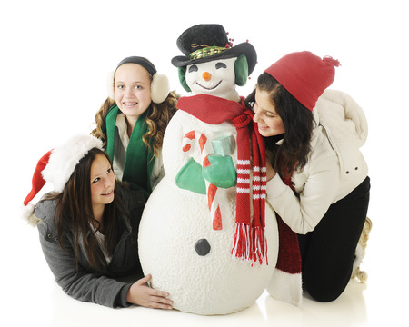 Three young teen girls playing around a Christmas snowman.  On a white background. photo
