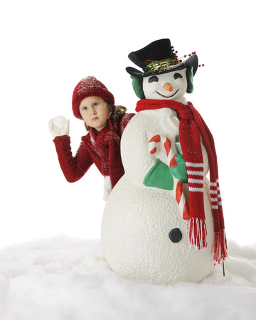 An elementary girl seriously contemplating the snowball throw shell take while hiding behind a Christmasy Snowman.  On a white background. photo