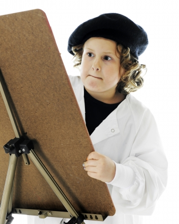 An elementary artist biting her lip as she concentrates on her work.  On a white background.