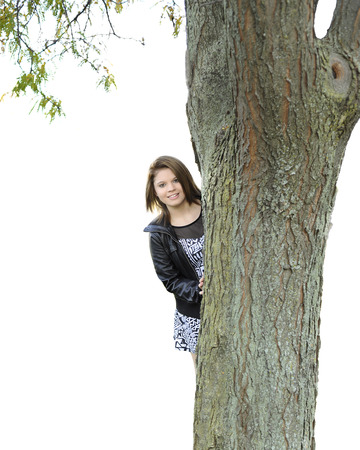 big tree: A beautiful young teen smiling at the viewer from behind a large tree.  Isolated on white.