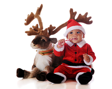 An adorable biracial Santa eating a candy cane by his reindeer.  Isolated on white.