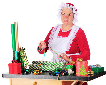 Mrs. Clause trying to decide which ribbon to put use with which wrapping paper as she wraps Christmas gifts.  On a white background.