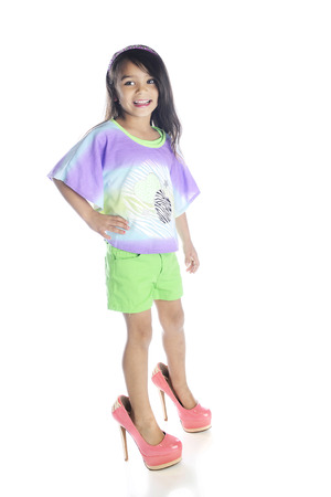 heals: A beautiful elementary girl happily wearing her mothers super high heals.  On a white background.