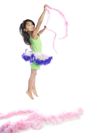 boas: A beautiful elementary girl jumping from and with fluffy pink boas.  On a white background. Stock Photo