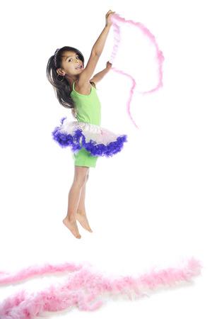 boas: Una bella ragazza elementare saltando da e con soffici rosa boa. Su uno sfondo bianco. Archivio Fotografico