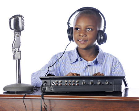 A handsome elementary boy in headphones happily managing a soundboard.  On a white background. Imagens