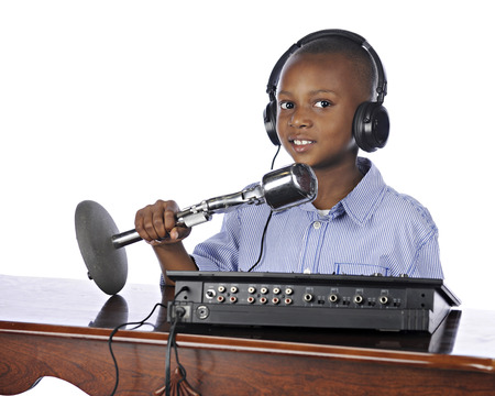A happy elementary boy sitting in front of a sound board with a mike and head phones.  On a white background. photo