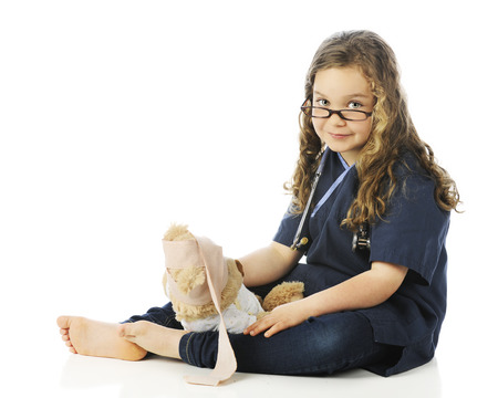 A pretty elementary girl in scrubs looking over her glasses as she bandages her teddy bears head.  On a white background. photo