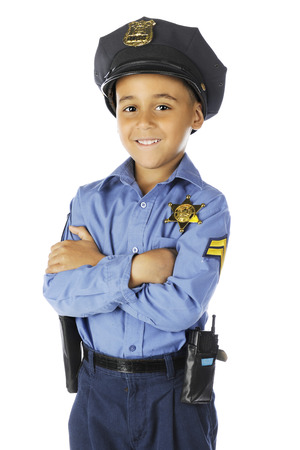 Front view of an elementary policeman smiling at the viewer with his arms folded.  On a white background. Imagens
