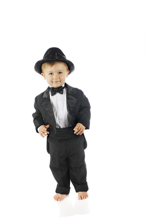 lapels: An adorable barefoot toddler all decked out in a black tuxedo and sparkly fedora.  On a white background.