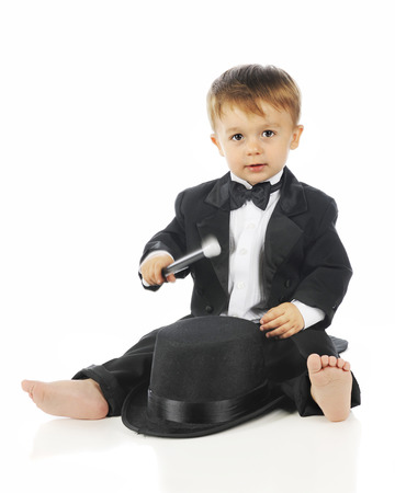 lapels: An adorable toddler sitting barefoot in his black tuxedo while happily drumming on his top hat.  On a white background.  Motion blur on his drumstick. Stock Photo
