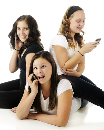 Three young teen friends texing or on the phone   The one on the floor is acting especially goofy   On a white background  photo