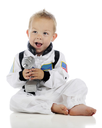 power drill: An adorable toddler astronaut in uniform happily holding a silver-colored power drill.  On a white background.