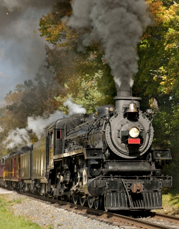 An old steam engine spewing dark smoke into trees in autumn colors on a sunny day.