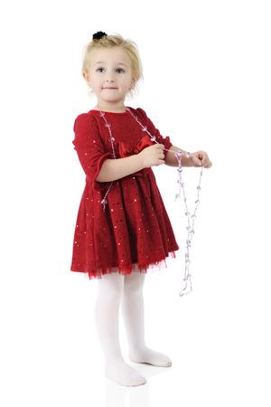 Een aanbiddelijke kleuter draagt een fonkelende rode jurk, terwijl gelukkig spelen met een streng van hart-vormige kralen. Op een witte achtergrond.