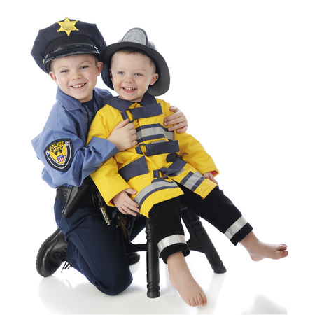 Little brothers posing together, the little one dressed as a fireman, the older his big brother dressed as a policeman.  On a white background