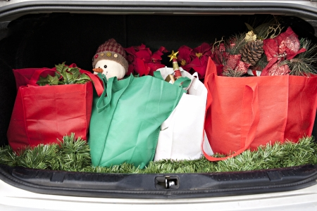 An opened car trunk filled with cloth bags full of gifts and decorations for Christmas.