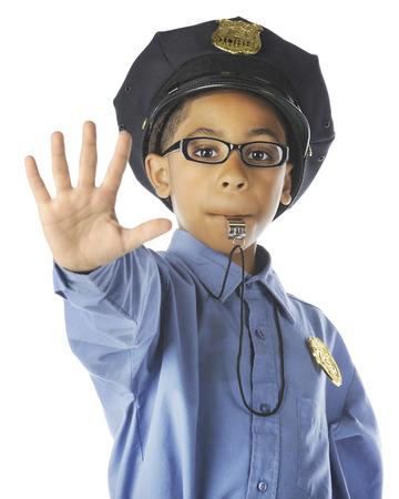 """Close-up van een elementair """"politieagent"""" blazen op zijn fluitje en gebaren stop. Op een witte achtergrond."""