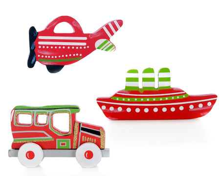 Three cutouts of an airplane, car and ship.  Each painted red, green and white.  The car also has sparkly gold trim.  On a white background. photo
