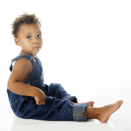 An adorable, but sad, biracial tot dressed only in denim overalls.  On a white background. Stock Photo - 24921725