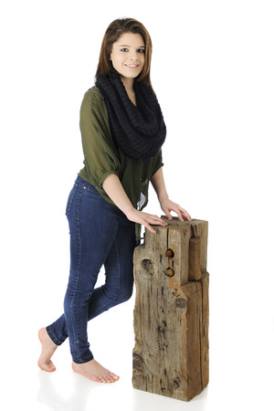 A beautiful barefoot teen happy and casual as she stand leaning on an old wooden beam.  photo
