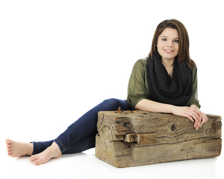A beautiful teen girl relaxed by an old, rustic wooden beam.  photo