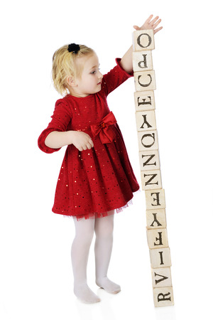 panty hose: An adorable and dressed up preschooler creating a tower out of alphabet blocks.  The tower is about ready to topple.