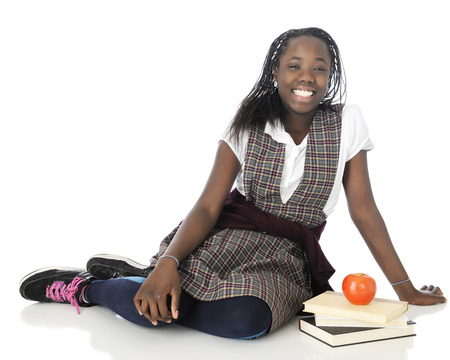 A happy tween girl relaxing on the floor in her school uniform, a small stack of books and an apple by her side.  photo