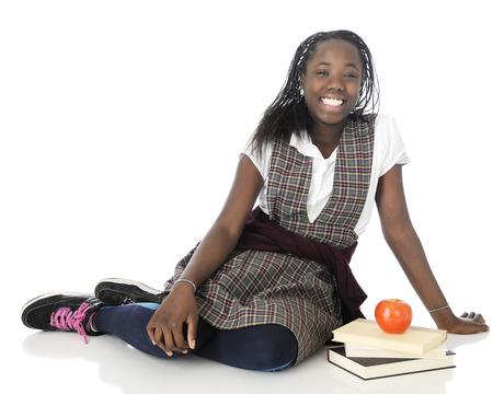 Une interpolation fille heureuse de détente sur le plancher dans son uniforme scolaire, une petite pile de livres et une pomme à côté d'elle. Banque d'images - 25221409