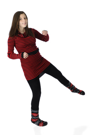 A pretty young teen dancing silly in her knit red and black striped dress and socks.  photo