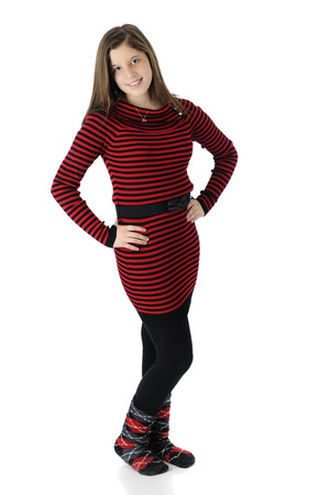 Full length image of a beautiful young teen in her knit red and black striped dress, black tights and crazy socks. Zdjęcie Seryjne - 25221402