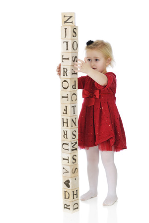 An adorable, dressed up preschool girl steading rustic alphabet blocks that shes stacked into a tower taller than herself.  Stock Photo