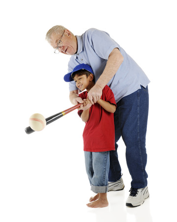 baseball caps: A senior and his preschool grandson working together to successfully bat a baseball.  On a white background.