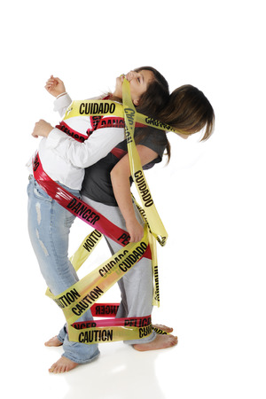 Two young teen girls struggling to free themselves from the Danger and Caution tape they're wrapped in.  Isolated on white. Stock fotó