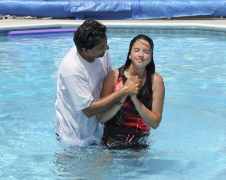 An Asian Indian pastor baptising a preteen in a swimming pool. Imagens