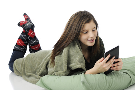A pretty young teen playing on her iPad while laying on her belly with a pillow and blanket.  On a white background. photo