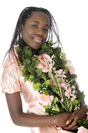 A beautiful tween girl adorning herself with leaves and flowers.  On a white background. Stock Photo