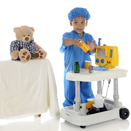 An adorable preschool  doctor  in blue scrubs questioning about the medication he should be giving his patient  toy bear  from his emergency cart   On a white background