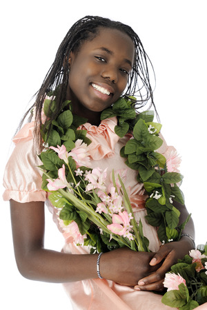 A beautiful tween girl dressed up in peach and adorned with leis of leaves and flowers   On a white background