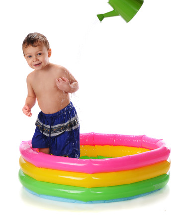 kiddie: A happy toddler in a kiddie pool getting sprinkled with a watering can   Isolated on white