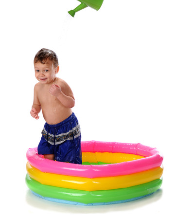 kiddie: A happy toddler in a kiddie pool getting doused by a watering can   Isolated on white