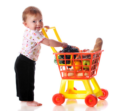 Una niña descalza compras en el supermercado con un carrito de juguete aislado en blanco
