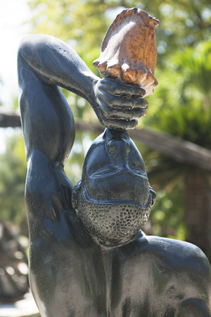 marron: A close-up and back view of a black Haitian statue, Le Negres Marron (unknown slave).  The slave is blowing into a conche shell, using it as a trumpet, to call the slaves together.  This is a historic statue signifying Haitis slave revolution that result