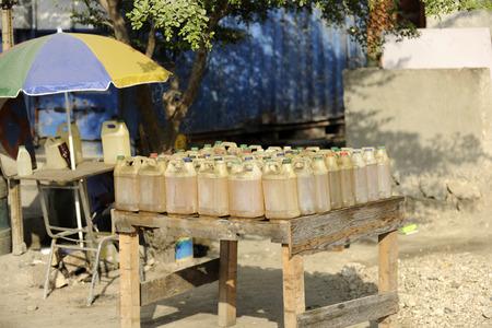 port au prince: Una mesa llena de uno garrafas llenas de gasolina a la venta en un puesto de lado de la calle, cerca de Port Au Prince, Hait�. Foto de archivo
